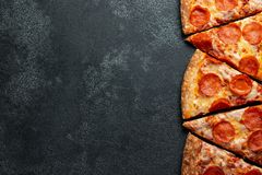 Cut into slices delicious fresh pizza with sausage pepperoni and cheese on a dark background. Top view with copy space for text. Pizza on the black concrete stock image