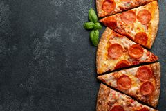 Cut into slices delicious fresh pizza with sausage pepperoni and. Cheese on a dark background. Top view with copy space for text. Pizza on the black concrete royalty free stock photos