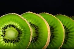 Cut slices of kiwi fruit close-up on black background horizontal Royalty Free Stock Image