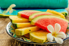 Cut slices of red and yellow watermelon decorated with a Plumeria or Frangipani flower on a colorful patterned ceramic plate stock photos
