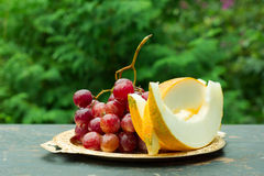 Cut slices of ripe yellow melon, and a bunch of grapes on a table with natural green background Royalty Free Stock Image