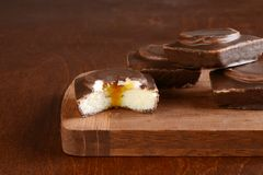 Cut small chocolate covered vanilla cake filled with cream and caramel sauce royalty free stock photography