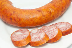 Cut smoked sausage on white plate Stock Photo