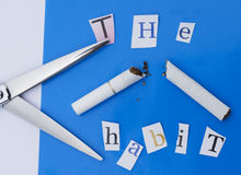 Cut the Smoking Habit. A pair of scissors, a broken cigarette and some letters from a magazine Stock Photo