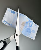 Cut spending. Euro bill being cut with scissors royalty free stock images