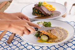 Cut steak. A female hand using knife cutting beef steak decorated with fries in a nice dish set on a table Stock Photos