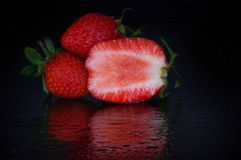 Cut strawberries with drops in reflection stock photo