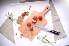 Cut strawberrries and cookies on a wooden carving board. Cut strawberrries, nuts, cookies and a knife on a wooden carving board on beige linen Royalty Free Stock Image