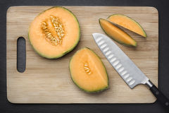 Cut sugar melon on a chopping board. Royalty Free Stock Photos