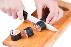 Cut sushi roll. Slicing sushi roll on wooden board isolated on white Royalty Free Stock Photography