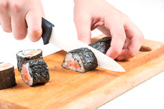 Cut sushi roll. Slicing sushi roll on wooden board isolated on white Stock Images