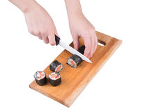Cut sushi roll. Slicing sushi roll on wooden board isolated on white Royalty Free Stock Photo