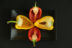 Cut sweet peppers seeds black plate stock images