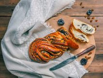 Cut sweet twisted bun with poppy seeds. Composition with raisins, prunes on a background of old wood, cloth and knife Royalty Free Stock Photos