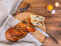 Cut sweet twisted bun with poppy seeds. Composition with raisins, prunes and egg on a background of old wood, cloth and Royalty Free Stock Photography