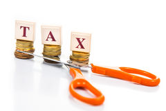 Cut taxes concept with coins and scissors Stock Images