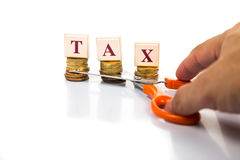 Cut taxes concept with coins and scissors Royalty Free Stock Photos