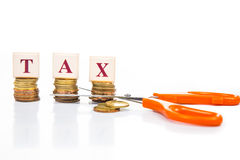 Cut taxes concept with coins and scissors Stock Photos