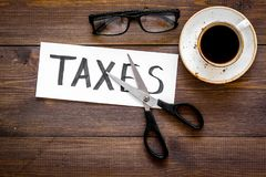 Cut taxes concept. Sciccors cut paper with word Taxes on dark wooden background top view copy space Stock Image
