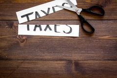 Cut taxes concept. Sciccors cut paper with word Taxes on dark wooden background top view copy space Stock Photo