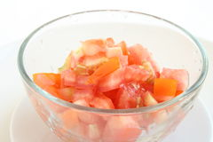 Cut tomato in a bowl. Cut red  tomato in a transparent  bowl Royalty Free Stock Photos