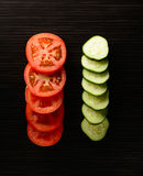 Cut tomato and cucumber with a knife Royalty Free Stock Image