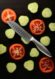 Cut tomato and cucumber with a knife Royalty Free Stock Images