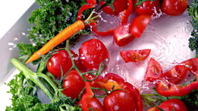 Cut tomato falling into water stock footage
