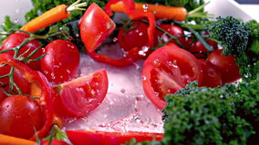 Cut tomato falling into water stock video footage