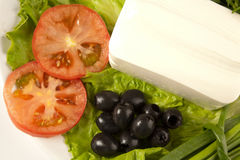 Cut tomato, olives, lettuce and feta cheese Royalty Free Stock Photography