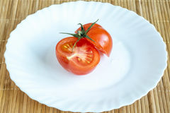 Cut tomato on white plate Stock Photography