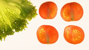 Cut tomatoes and lettuce on white background, ecological products, gmo free. Stock footage stock video footage
