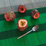 Cut top of one full passionfruit and three empty fruits with a spoon at side on bamboo mats Royalty Free Stock Images