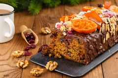 Cut traditional christmas fruit cake pudding in chocolate glaze. Cut traditional christmas fruit cake pudding with in chocolate glaze decorated with cranberries Stock Photo