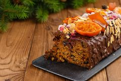 Cut traditional christmas fruit cake pudding in chocolate glaze. Cut traditional christmas fruit cake pudding with in chocolate glaze decorated with cranberries Stock Photos