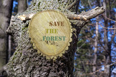 Cut tree branch  with sign save the forest. Cut tree   with  sign save the forest Royalty Free Stock Image