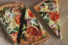 Cut into triangular pieces of quiche with eggs, fresh spinach, t. Omatoes, bacon and cheese Royalty Free Stock Photo
