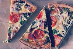 Cut into triangular pieces of quiche with eggs, fresh spinach, t. Omatoes, bacon and cheese Stock Photo