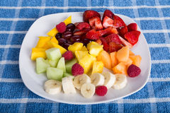 Cut Tropical Fruit on White Plate and Blue Towel Stock Photography