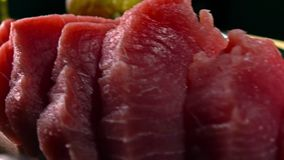 Cut tuna fillet pieces on wooden board. 4K close-up dolly video. Cut tuna fillet pieces on wooden board. 4K close-up dolly shot stock footage