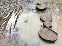 Wooden stepping stones sit in mud with a puddle to the Royalty Free Stock Photo