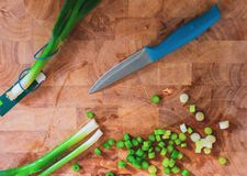 Cut up spring onions on a wooden chopping board next to a sharp blue knife stock image