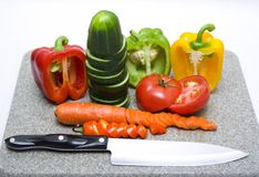 Cut vegetables. A cutting board with cut vegetables and a knife royalty free stock image