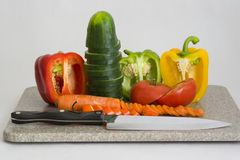 Cut vegetables. A cutting board with vegetables and a chefs knife royalty free stock image