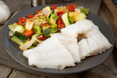 Cut vegetables and grilled fish in classic wood Stock Images
