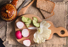 The cut vegetables on an old wooden table. Rural style, close up, dark background. A flower from a bulb, radishes and a cucumber, the cut with krudochka Stock Photo