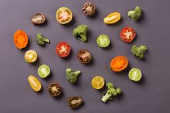 Cut tomatoes and broccoli on grey background stock images