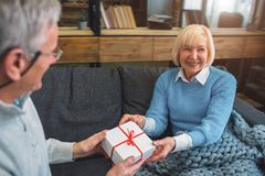 Cut view of nice and cute grandparents. He is giving a gift to h. Is wife. She is receiving that with emotions and pleasure stock photography