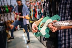 Cut view of two young men playing on electric guitars. First one hold green one. Second guy hold brown guitar and has. One leg higher then another stock photos