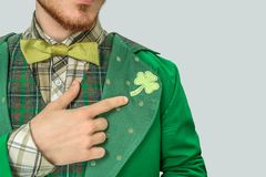 Cut view of young bearded man point on clover on suit. He wear saint Patrick`s costume. on grey background. stock photos